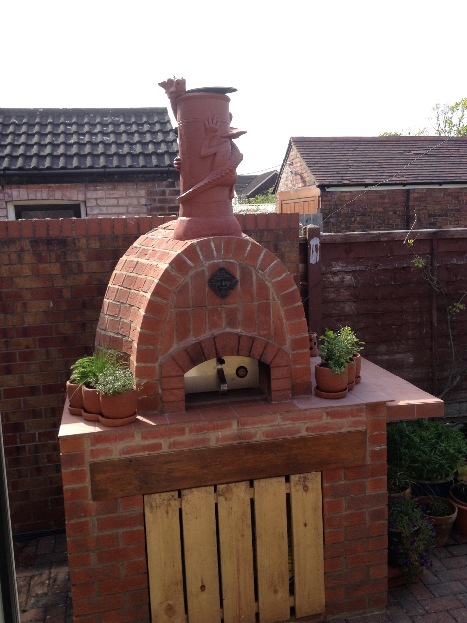 terracotta dragon chimney pot installed on a pizza oven